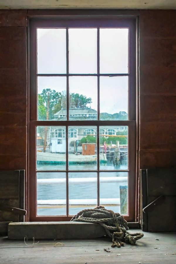 用放置在架子的绳索观看肮脏的脏的paned窗口在从车间大厦的下雨天对其他小游艇船坞大厦和 图库摄影