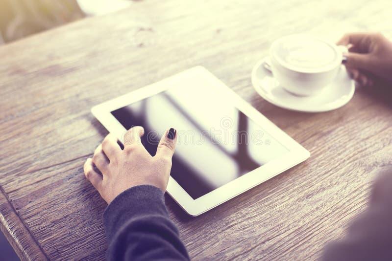 用数字式片剂和一杯咖啡在一张木桌上的女孩 图库摄影