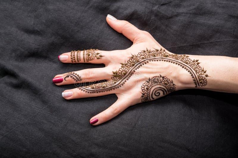 用无刺指甲花装饰的人的手的图片 免版税库存照片