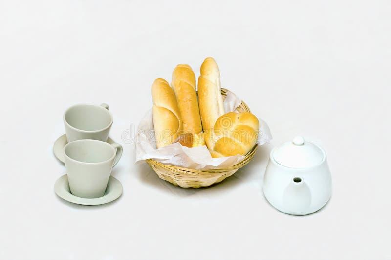 用早餐与一个充分的面包篮子杯子和茶壶在白色 免版税图库摄影