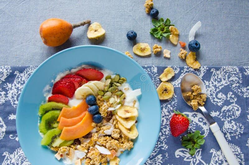 用早餐与坚果、番木瓜、猕猴桃、草莓、香蕉和蓝莓 库存图片