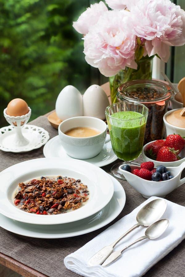用早餐与家庭做的格兰诺拉麦片、绿色圆滑的人和莓果 免版税库存照片