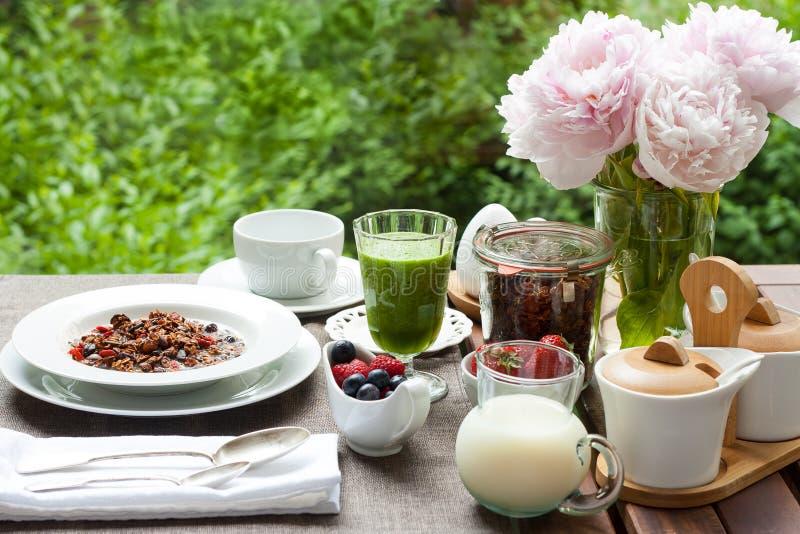 用早餐与家庭做的格兰诺拉麦片、绿色圆滑的人和莓果 库存图片