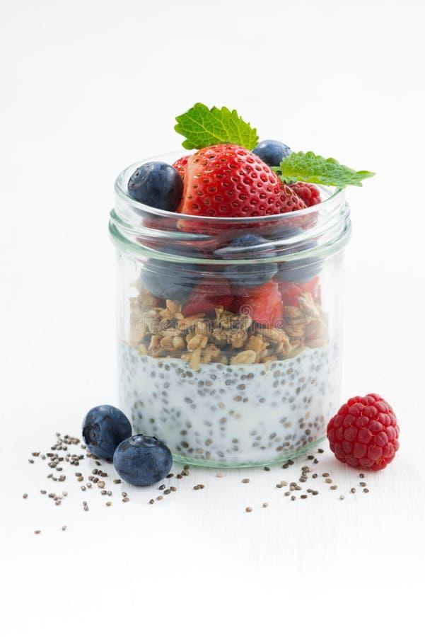 用早餐在一个玻璃瓶子、chia用莓果和燕麦剥落 库存图片