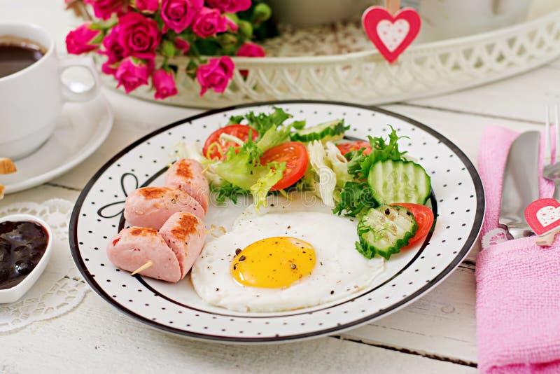 用早餐在华伦泰` s天-以心脏、多士、香肠和新鲜蔬菜的形式煎蛋 咖啡 免版税图库摄影