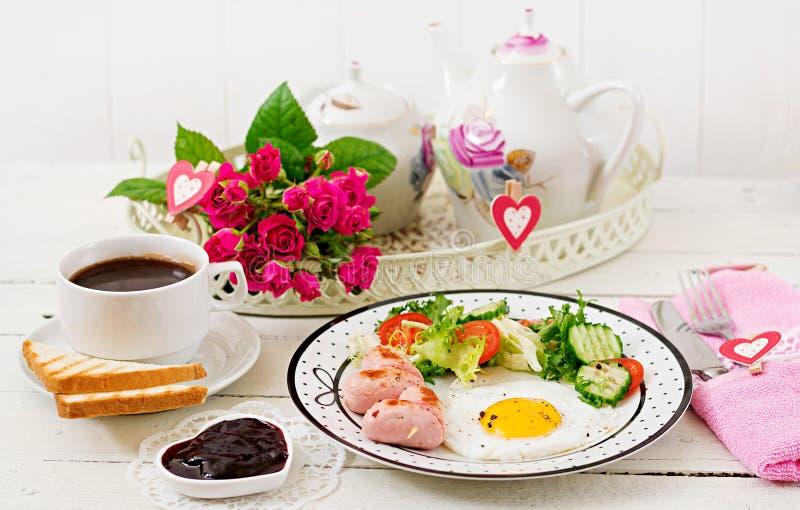 用早餐在华伦泰` s天-以心脏、多士、香肠和新鲜蔬菜的形式煎蛋 图库摄影