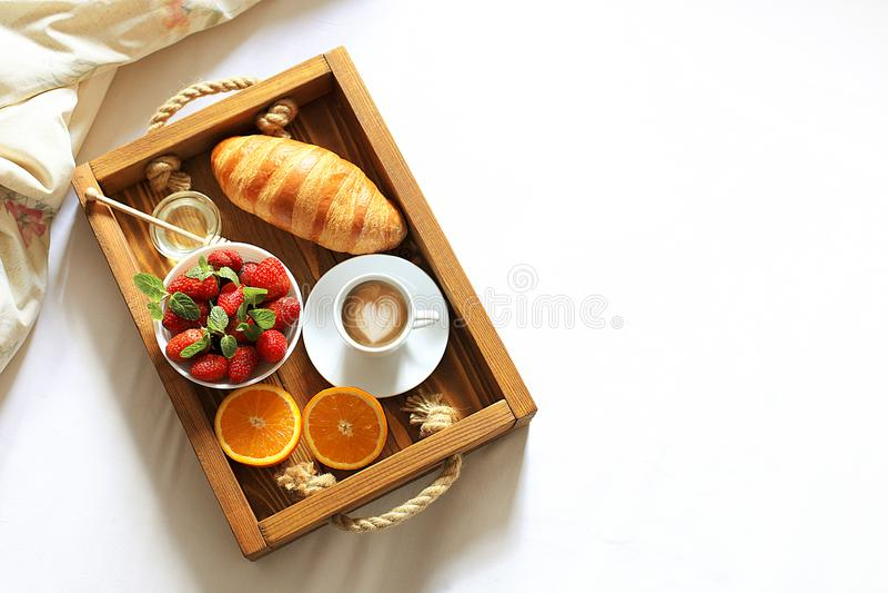 用早餐在有咖啡的床盘子、新鲜的法国新月形面包和果子在白色板料顶视图,拷贝空间 蜜月 Mornin 免版税库存图片