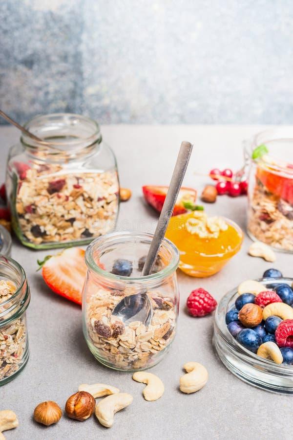 用早餐在瓶子、准备用新鲜的莓果,坚果和muesli 库存照片
