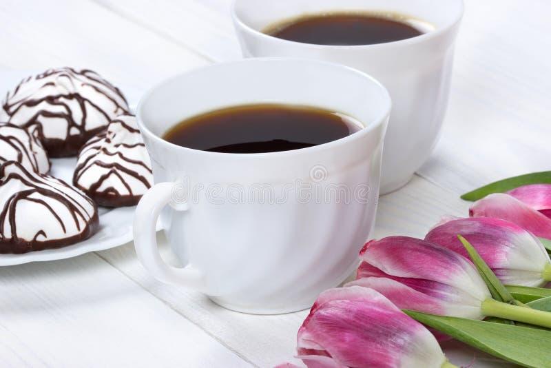 用早餐用咖啡、新鲜的郁金香和蛋糕在木桌上 库存图片