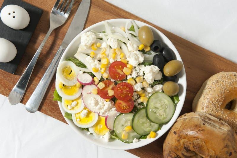 用早餐用咖啡、百吉卷、沙拉和鸡蛋 库存照片