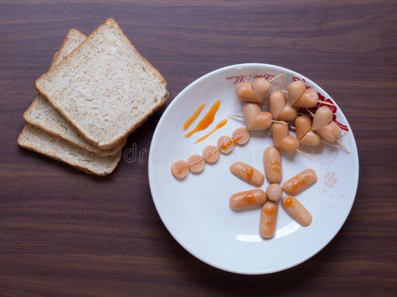 用早餐用在桌上的面包和心脏香肠 免版税库存图片