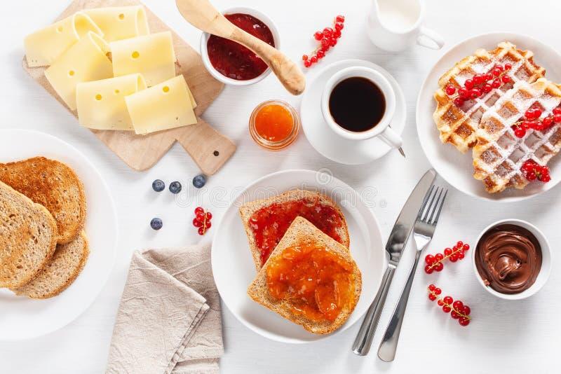 用早餐用奶蛋烘饼、多士、莓果、果酱、巧克力传播和c 图库摄影