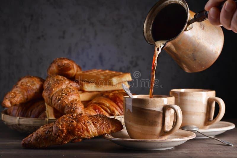 用早餐用无奶咖啡、新近地被烘烤的奶蛋烘饼和新月形面包 库存照片