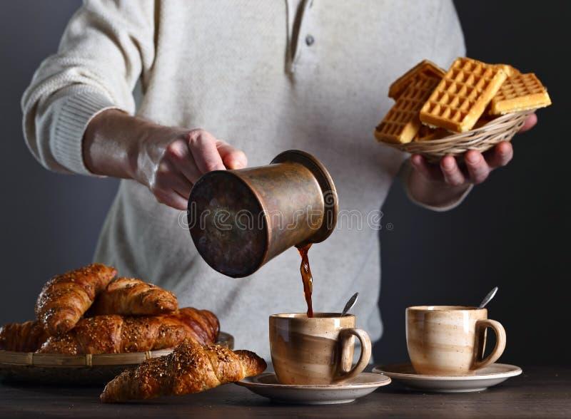 用早餐用无奶咖啡、新近地被烘烤的奶蛋烘饼和新月形面包 库存图片