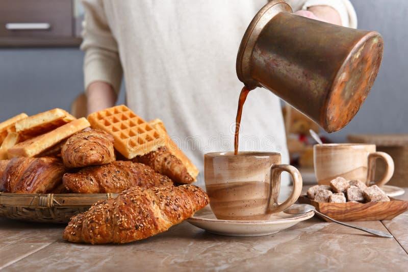 用早餐用无奶咖啡、新近地被烘烤的奶蛋烘饼和新月形面包 免版税库存照片