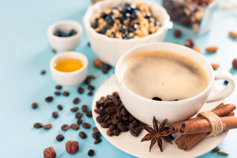 用早餐用燕麦粥粥、咖啡杯和果子在蓝色木背景 健康早餐概念 顶视图 免版税库存照片
