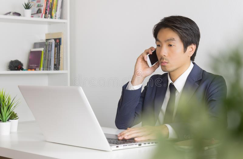 用智能手机和笔记本电脑在办公的正装亚洲商人肖像 库存图片
