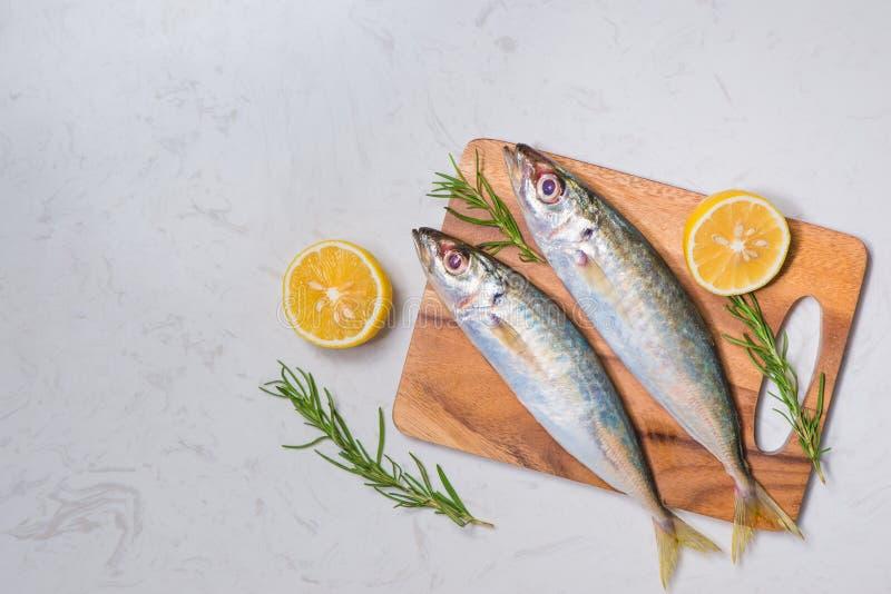 用柠檬切片和草本装饰的新鲜的生鱼在木桌上 库存图片