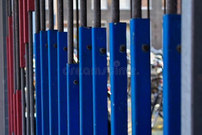 用栏杆围蓝色和红色板材的老灰色金属 免版税库存照片