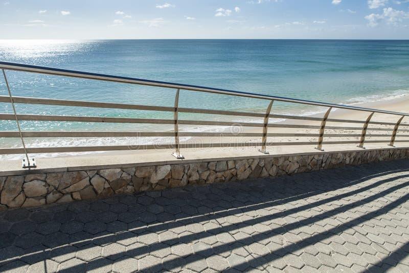 用栏杆围在旁边在海滩附近的一条路 免版税库存照片