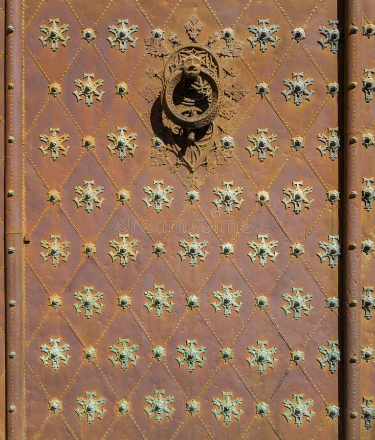 用样式和铆钉门华丽地装饰的老生锈 免版税库存图片