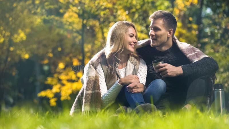 用格子花呢披肩报道的夫妇坐在秋天公园,饮用的热的茶和谈话 库存照片