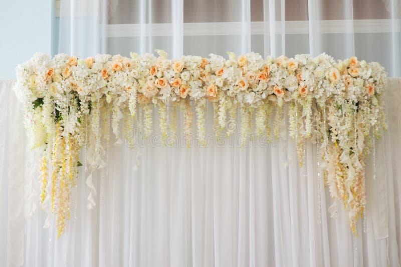 用桃红色和白花装饰的美丽的婚礼曲拱户内 图库摄影