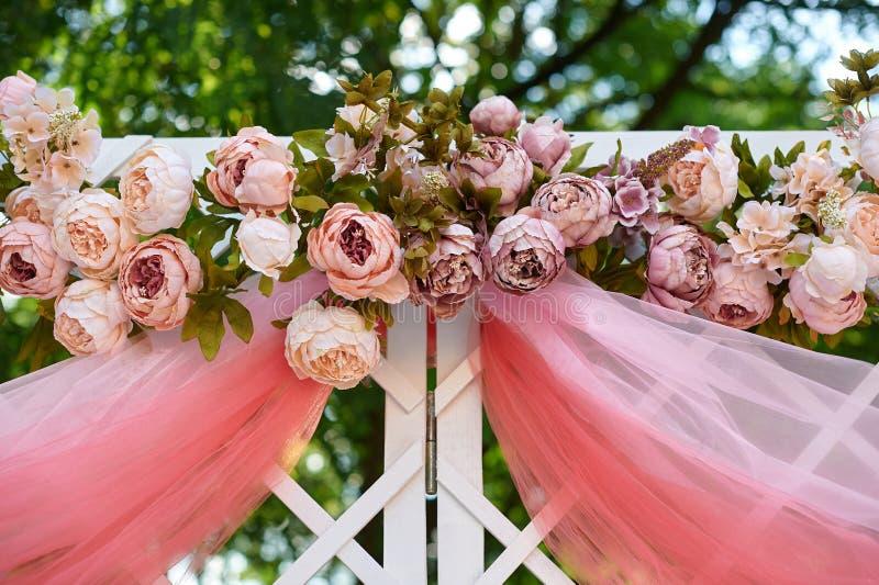 用桃红色和红色花装饰的美丽的白色婚礼曲拱户外 库存照片