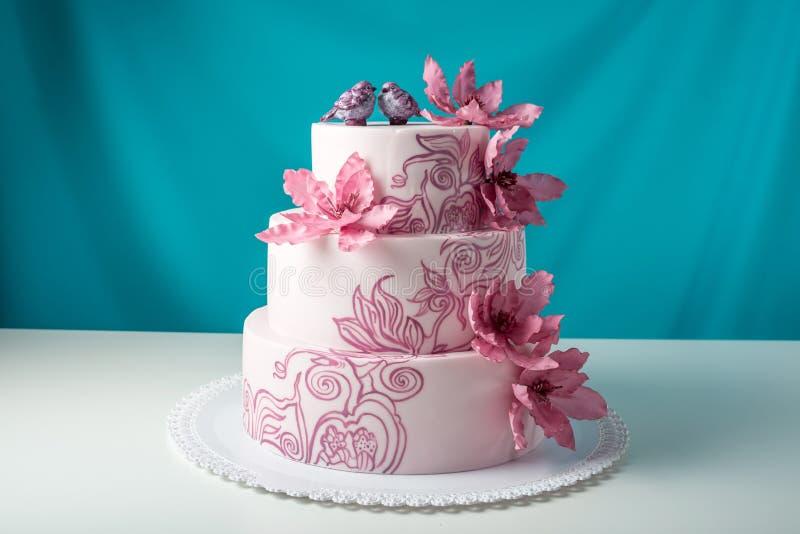用桃红色花装饰的一个美好的家庭婚礼三层蛋糕 免版税库存照片