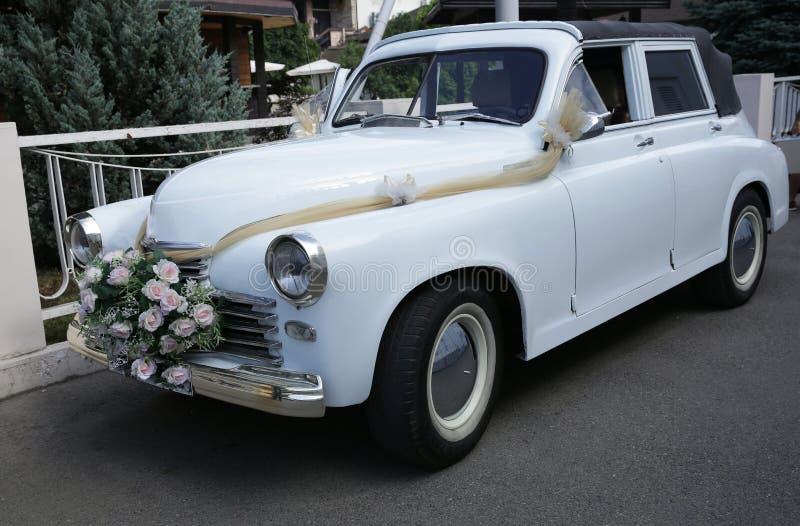 用桃红色花装饰的婚姻的减速火箭的白色汽车 r 图库摄影