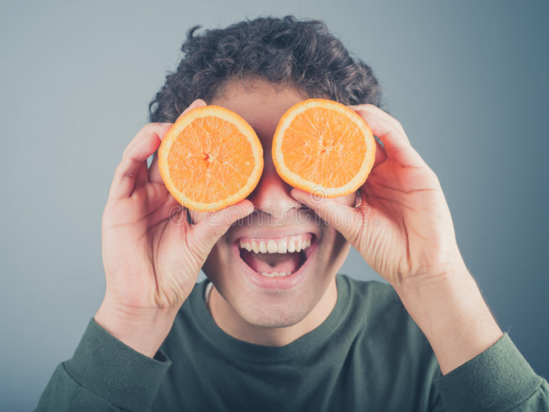 用桔子的傻的年轻人作为双筒望远镜 免版税库存图片