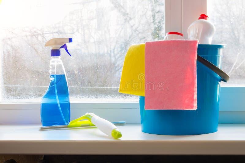用桶提浪花和橡皮刮板窗户清洁的在窗口基石 库存照片