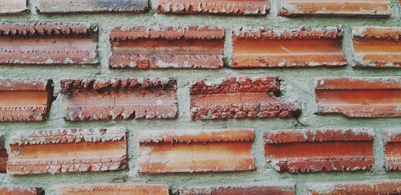 用棕色砖墙贴背景,有些砖墙破裂 免版税库存照片