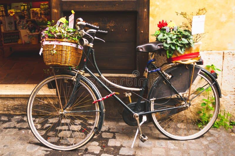 用植物装饰的经典自行车停放在与软和温暖的口气的一个商店门前面 库存照片
