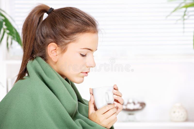 用毯子在家包括的妇女饮用的茶 免版税库存图片