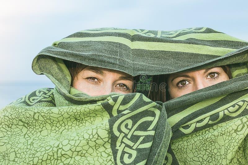 用毯子盖的两个女孩 用面纱和神奇神色盖的妇女 库存图片