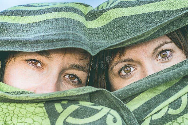 用毯子盖的两个女孩 用面纱和神奇神色盖的妇女 免版税库存照片