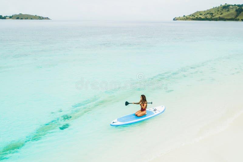 用浆划在一口板的妇女在热带海岛附近 免版税库存图片