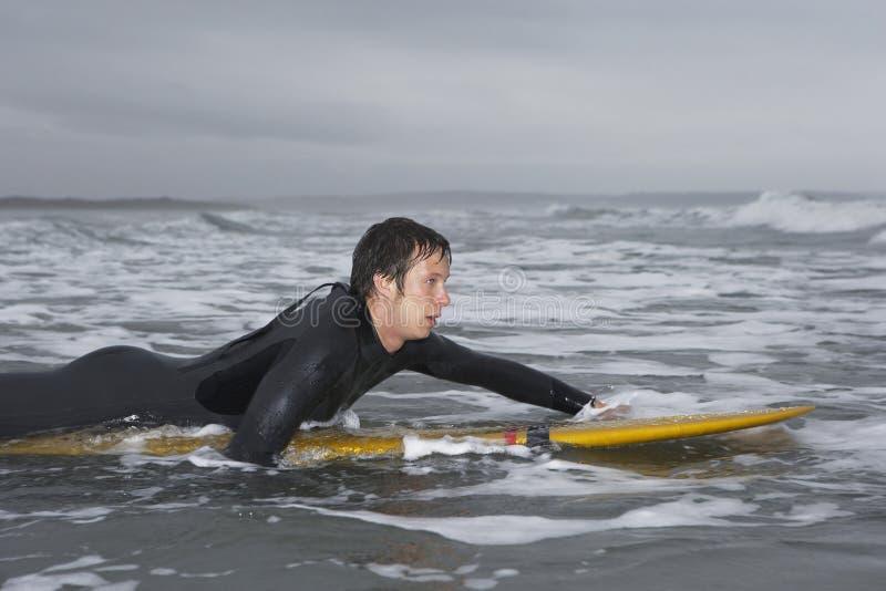 用浆划在冲浪板的男性冲浪者在水中在海滩 库存照片