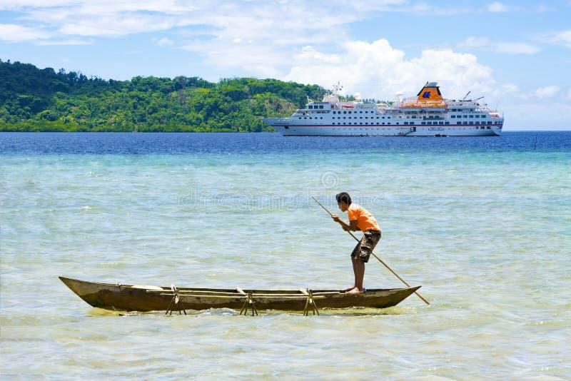 用浆划在巡航划线员,所罗门群岛前面的当地男孩手工制造独木舟 免版税库存图片