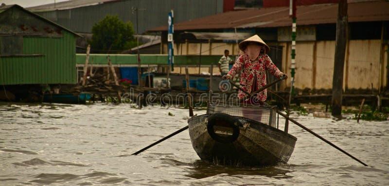 用浆划在湄公河,越南的越南妇女 免版税库存照片