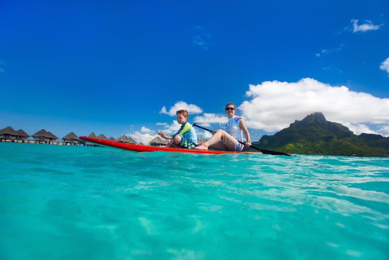 用浆划在热带海洋的家庭 库存照片