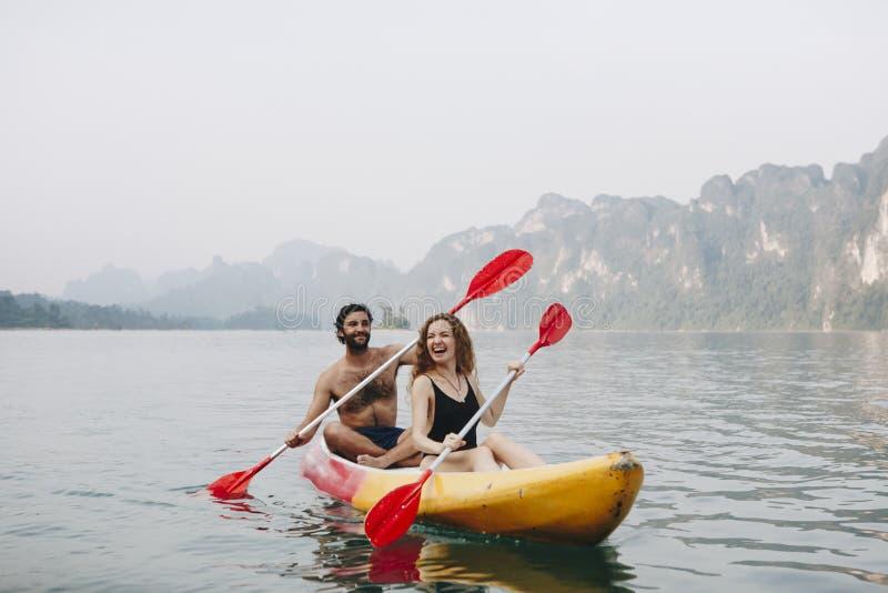 用浆划在独木舟的一对年轻夫妇 免版税库存照片