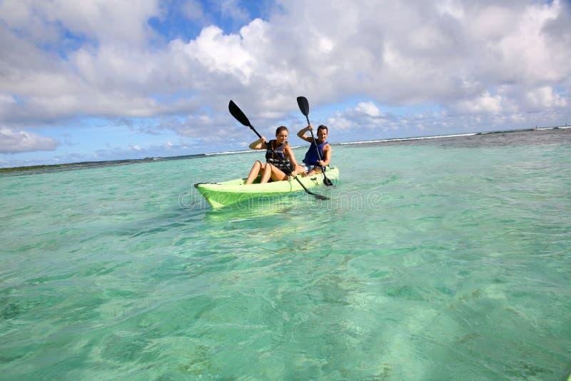 用浆划在独木舟的夫妇在热带 免版税库存照片