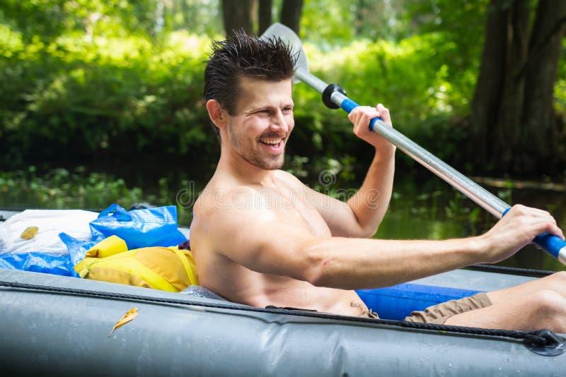 用浆划在皮船的一个微笑的人桨在河漂流期间 划皮船的 荡桨桨的独木舟的人 免版税库存照片