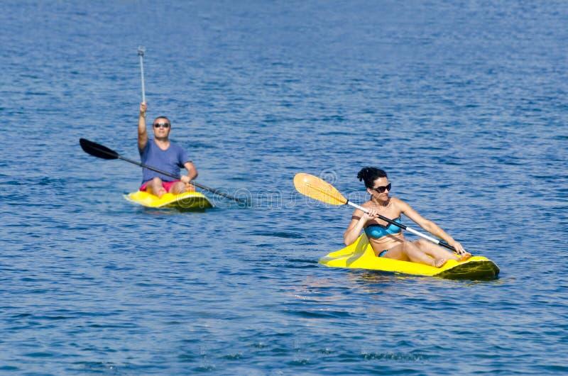 用浆划在皮船的快乐的夫妇在爱奥尼亚海 库存照片