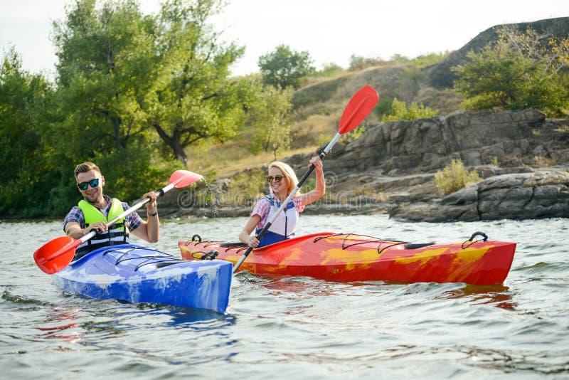 用浆划在美丽的河或湖的年轻愉快的夫妇皮船 库存照片