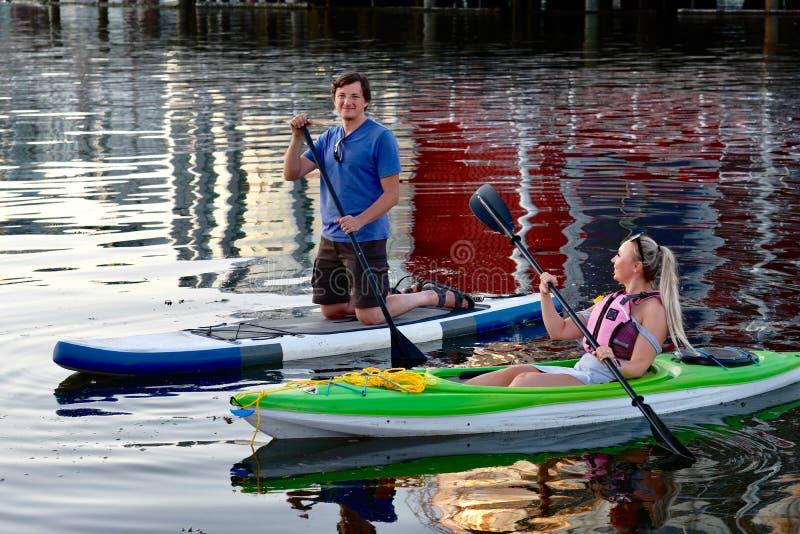 用浆划在英吉利湾的已婚夫妇获得乐趣 免版税图库摄影