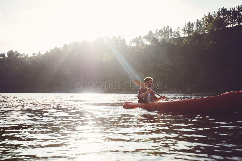 用浆划皮船的人在一个夏日 图库摄影
