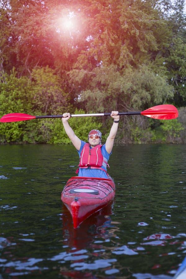 用浆划皮船的人背面图在有妇女的湖在背景中 在湖结合划皮船在一个晴天 库存照片